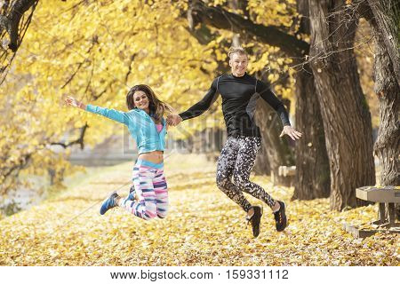 Beautiful Young Couple Celebrate And Jumping After Successful Training In The Park. Autumn Environme