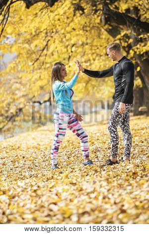 Beautiful Young Couple Celebrate After Successful Running In The Park. Autumn Environment.