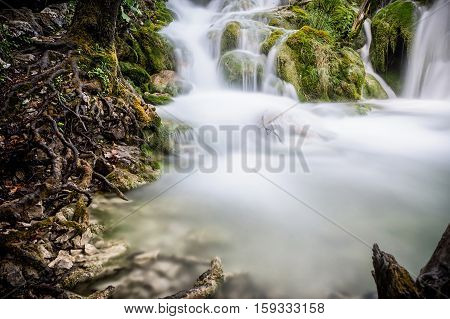 Small peaceful cascade waterfall with silky water