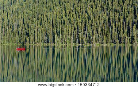 A bright red canoe glides past a lush green coniferous forest, reflected in the still waters of Lake Louise, Alberta, Canada