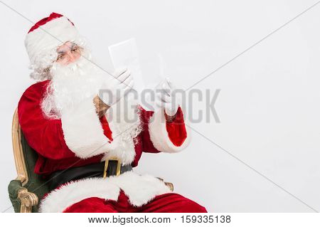 Santa Claus Reading Letter isolated over white baclground.