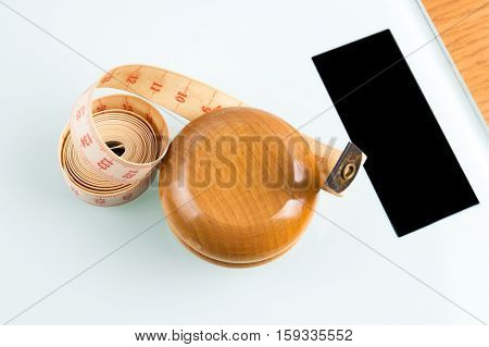 Yo-yo effect in diet concept. Wooden yoyo with centimeter measure. Bathroom weight scale with black display screen.
