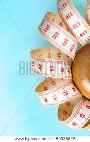 Yo-yo effect in diet concept. Wooden yoyo with centimeter measure. Vertical orientation. Blue pastel background. Copy space on the left.