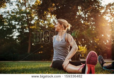 Fit young woman exercising at park. Fit young woman doing stretching workout in morning.