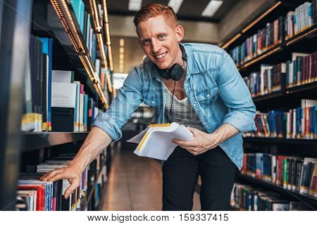 Young caucasian man finding books in public library. Finding information for his studies.