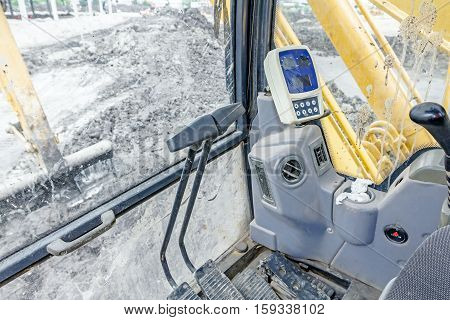 Control system in excavator's cabin dashboard with and windscreen glass.
