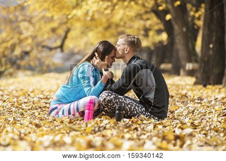 Beautiful Young Couple Resting And Kissing After Successful Training In The Park. Autumn Environment