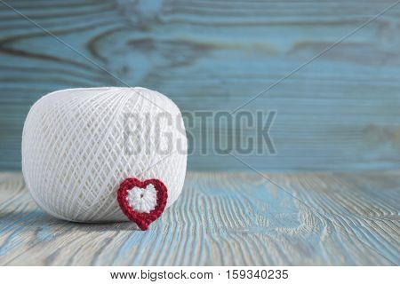 White ball of eco natural cotton yarn for knitting crochet and knitted flower and heart. Rustic blue wooden background Irish crochet lace elements