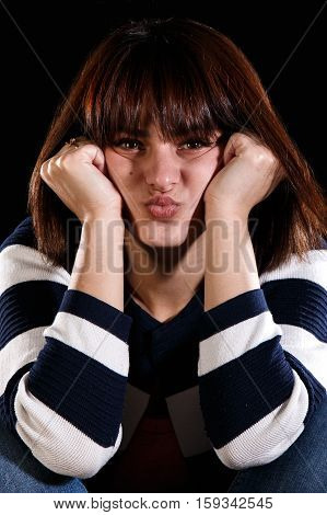 Unhappy cute young girl over black background