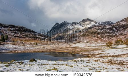 Wintery scene taken at Blea Tarn in Cumbria on the Little Langdale to Great Langdale road. It has a backdrop of the Langdale Pikes