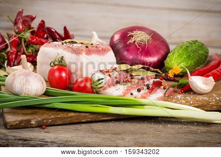 Closeup of salted lard with spices and vegetables on wooden cutting board