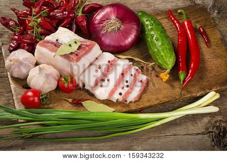 salted lard with spices, green onion and vegetables on wooden cutting board