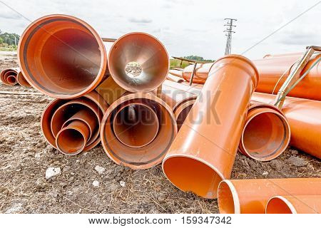 Arranged sewer pipes are waiting to be placed into the ditch at construction site.