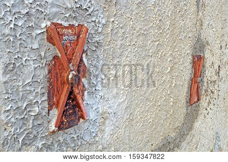 Facade of an old italian masonry building with metal tie-rod and anchor plate