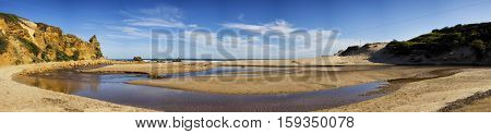 Panorama of a yellow sand rock and beach at Alreys inlet, Australia
