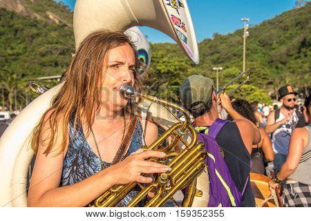 27 November, 2016. The woman playing contrabass in the street at sunny day at Festival Fanfare Activist Festival de Fanfarras Ativistas - HONK RiO 2016 at Leme district, Rio de Janeiro, Brazil