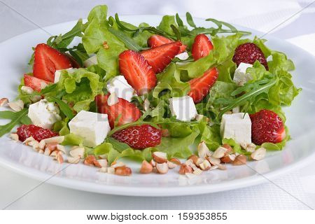 Salad of lettuce arugula strawberries feta cheese and peanuts