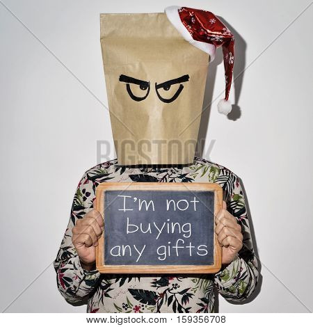 a young man dressing casual wear with a paper bag in his head and a santa hat in the top shows a chalkboard with the text I am not buying any gifts written on it