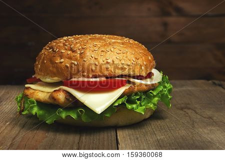 Home made hamburger on wooden background. Fastfood meal. Vintage toned