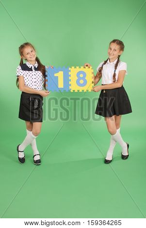 Two school girls hold color board with the number eighteen on green