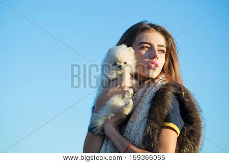 Pretty girl young beautiful woman in fur vest keeps cute small dog pet in hands outdoors on blue sky