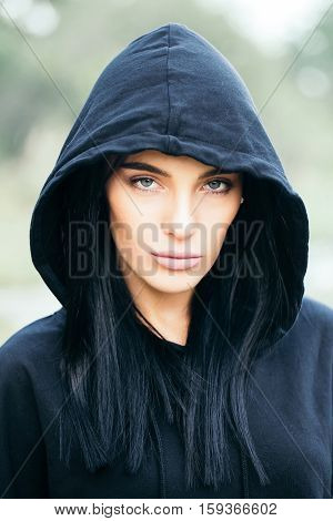 young pretty woman or fashionable sexy girl with cute face and brunette hair in black jacket with hood outdoor on blurred or defocused background