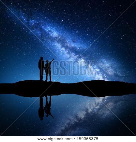 Milky Way with silhouette of a family. Father and a son who pointing finger in night starry sky on the mountain near the river with sky reflection in water. Night landscape. Space. Milky way with men