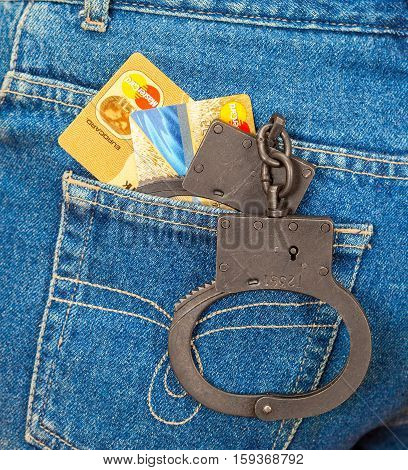 MOSCOW RUSSIA - NOVEMBER 27 2016: Black metal handcuffs and credit cards in back jeans pocket