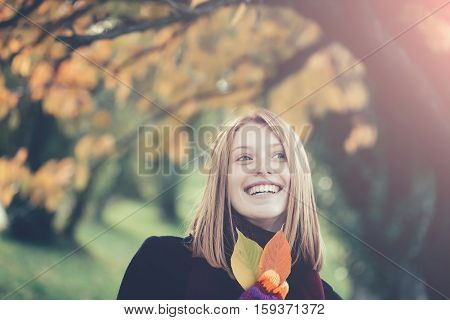 Pretty girl young beautiful woman with red hair and yellow leaves outdoors in autumn park on natural background