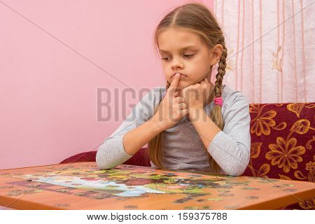 The Child Is Thinking How To Assemble A Picture From Puzzles
