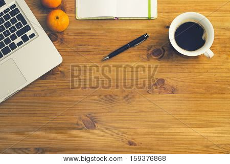 pc on wooden desk with blank white book