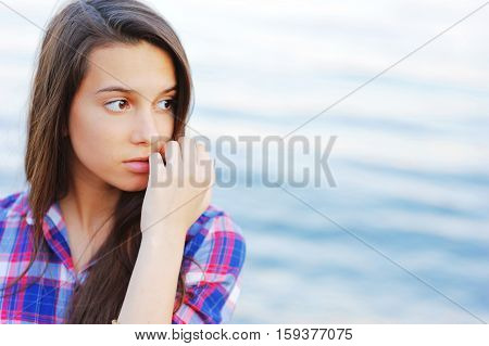 Portrait of young attractive long-haired girl in the shirt in the box with sad brown eyes on blurred background of the river closeup.