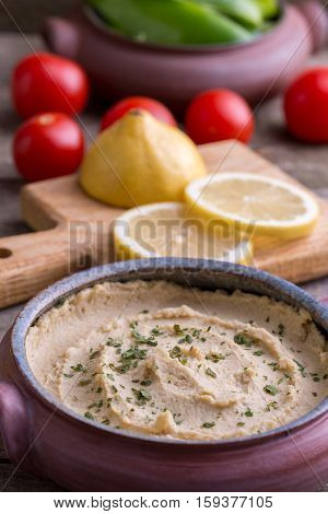 Humus in homemade bowl with vegetable around.