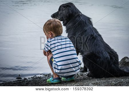 Big Black Dog And His Little Boy.