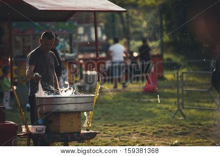 Man making candy floss on a candy floss machine. Cotton candy making and selling at an amusement park. Sugary sweet cotton candy, children's favorite.