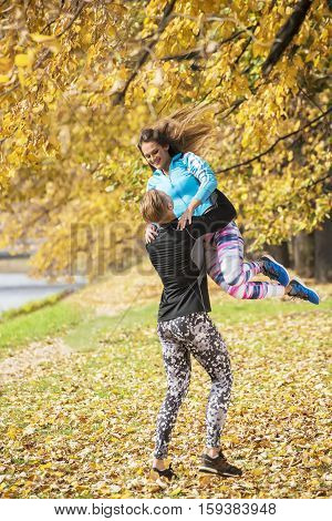 Beautiful Young Couple Enjoying Together In The Park. Autumn Environment.