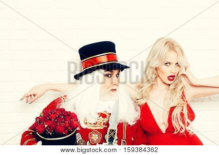 Senior man beefeater yeomen warder in uniform and pretty girl young sexy blond woman on white brick wall