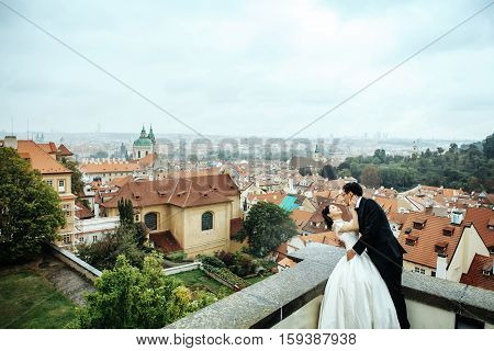 Chinese bride and groom young cute newlyweds just married couple hug outdoors on roof on cityscape background