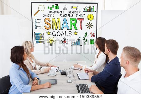Group Of Businesspeople Looking At Smart Goals Concept On Projector Screen In Conference Room