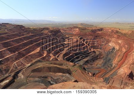Overview of the  largest of the many open cut pits at Tom Price iron ore mine in the Pilbara region of Western Australia. Haul roads and ramps can be seen on either side of the pit.