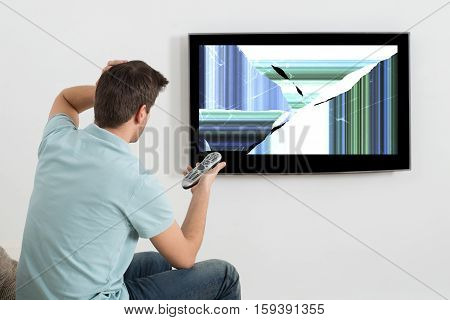 Frustrated Man Sitting On Sofa In Front Of Television Showing Distorted Screen