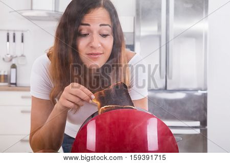 Young Woman Taking Slice Of Burnt Toast Out Of The Toaster In Kitchen