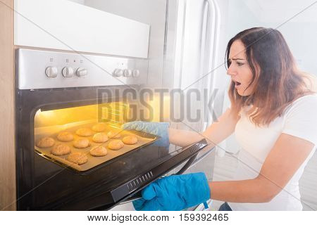Young Shocked Woman Looking At Burnt Cookies From Oven