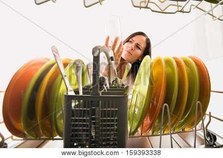 Young Unhappy Woman Looking At Clean Glass In Dishwasher