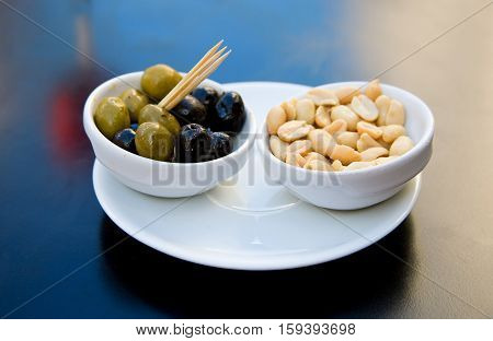 Nibbles to an aperitif: black and green olives and salt peanuts