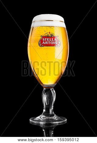 LONDON UK -NOVEMBER 29. 2016 Cold glass of Stella Artois beer on black background prominent brand of Anheuser-Busch InBev is a pilsner brewed in Leuven Belgium since 1926
