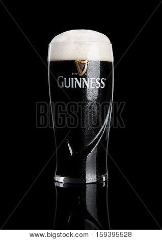 LONDON UK - NOVEMBER 29 2016: Glass of Guinness original beer on black background. Guinness beer has been produced since 1759 in Dublin Ireland.