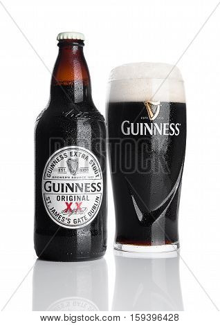 LONDON UK - NOVEMBER 29 2016: Guinness extra stout beer bottle and glass on white background. Guinness beer has been produced since 1759 in Dublin Ireland.