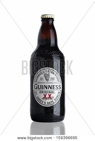 LONDON UK - NOVEMBER 29 2016: Guinness extra stout beer bottle on white background. Guinness beer has been produced since 1759 in Dublin Ireland.