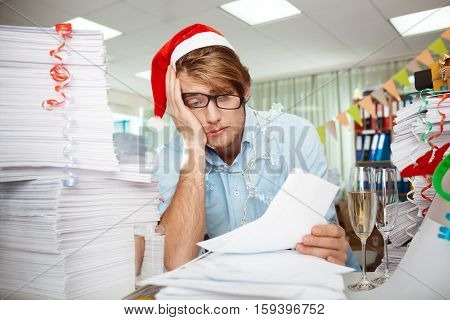 Tired young handsome businessman in red santa claus hat sitting at workplace among papers on christmas day.